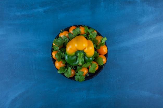 Piatto nero di peperone e pomodorini sul tavolo blu.
