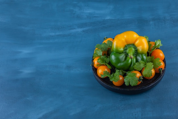 Black plate of bell pepper and cherry tomatoes on blue.