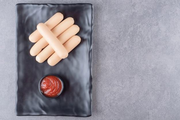 Un piatto nero di salsicce bollite con ketchup