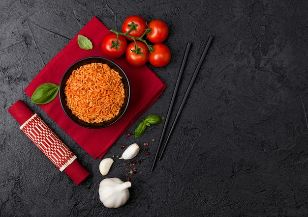 Black plate bowl of rice with tomato and basil and garlic and chopsticks on red napkin and bamboo place mat. top view.