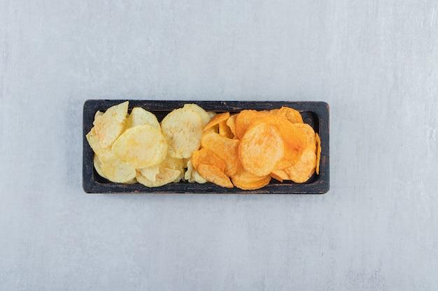 Piatto nero di vari chip deliziosi sulla pietra.