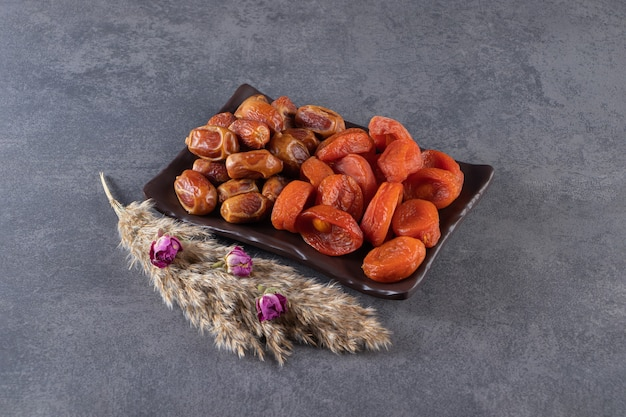 Black plate of dried organic dates and apricots on stone surface.