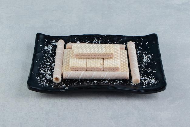 A black plate full of crusty waffle rolls.