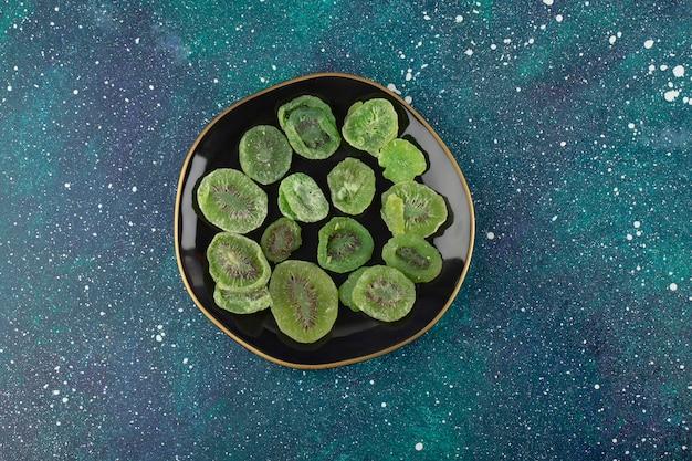 Un piatto nero pieno di kiwi secchi.