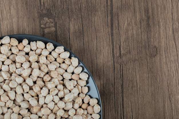 A black plate full of dried raw white peas on wooden table .