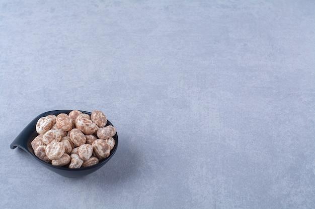 Un piatto nero pieno di cereali sani sul tavolo grigio.