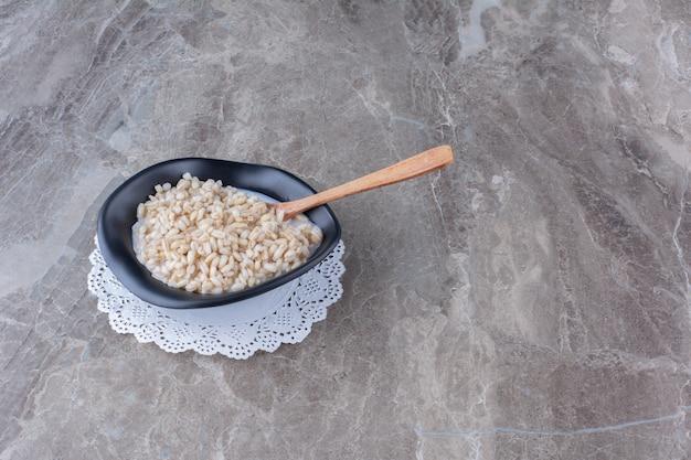 Un piatto nero pieno di cereali sani con latte e un cucchiaio di legno.