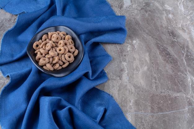 Un piatto nero di anelli di cereali al cioccolato sani per la colazione.