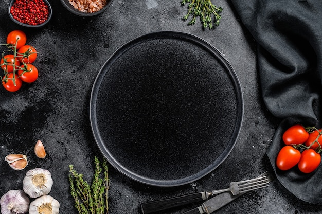 新鮮な生の野菜、野菜の中央にある黒いプレート。健康的でクリーンな食事、ビーガン、ダイエット食品のコンセプト。黒の背景