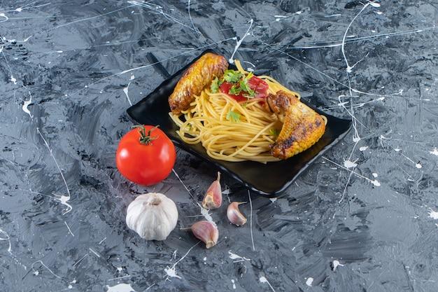 Piatto nero di tagliatelle con ali di pollo fritte su superficie di marmo.
