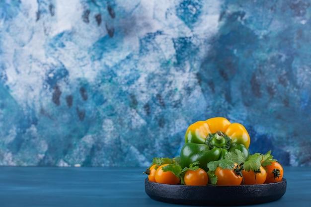 Черная тарелка болгарского перца и помидоров черри на синем фоне.