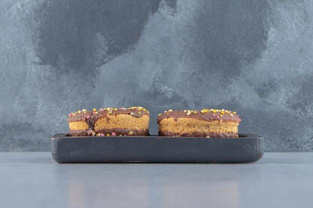 돌 배경에 초콜릿 도넛의 검은 접시. 고품질 사진