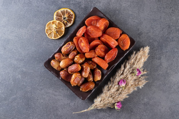 Черная тарелка сушеных органических фиников и абрикосов на каменной поверхности.