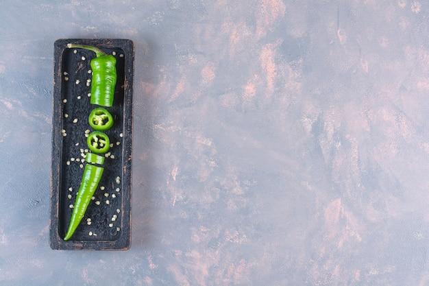 Черная тарелка свежего зеленого перца чили на каменной поверхности