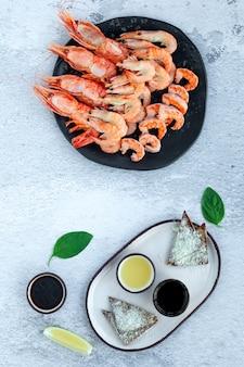 Черная тарелка свежих сырых королевских креветок и вареных креветок джамбо с соусами