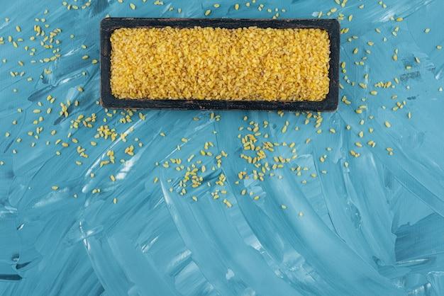 파란색 배경에 원시 마른 쌀의 검은 접시.