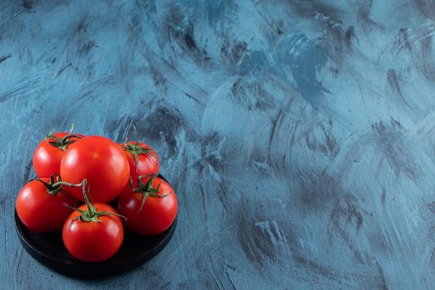 Черная тарелка красных свежих помидоров на синем фоне.