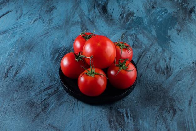 Черная тарелка красных свежих помидоров на синей поверхности.
