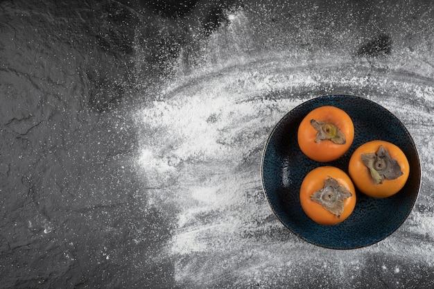 Черная тарелка спелых фруктов хурмы на черной поверхности