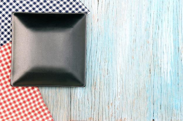 나무 테이블 배경에 식탁보에 검은 접시
