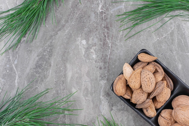 Black plate of organic shelled almonds on marble surface.