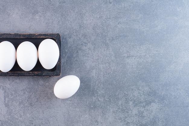 Piatto nero di uova bianche organiche sul tavolo di pietra.