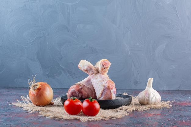 Piatto nero di parti di pollo crudo con verdure sulla superficie di marmo.