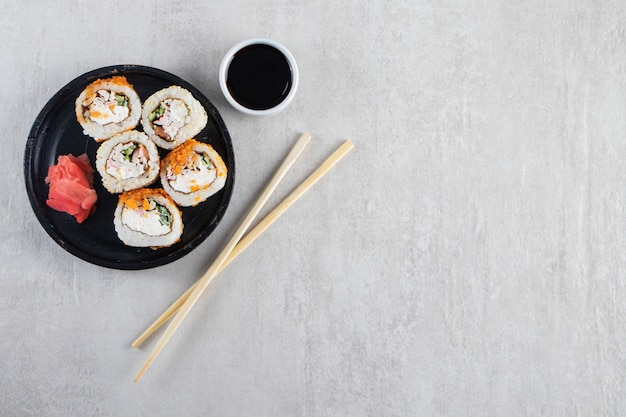 Black plate of sushi rolls with chips and crab on stone background.
