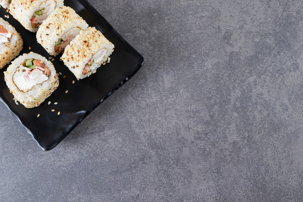 Piatto nero di sushi rotoli con semi di sesamo su sfondo di pietra.