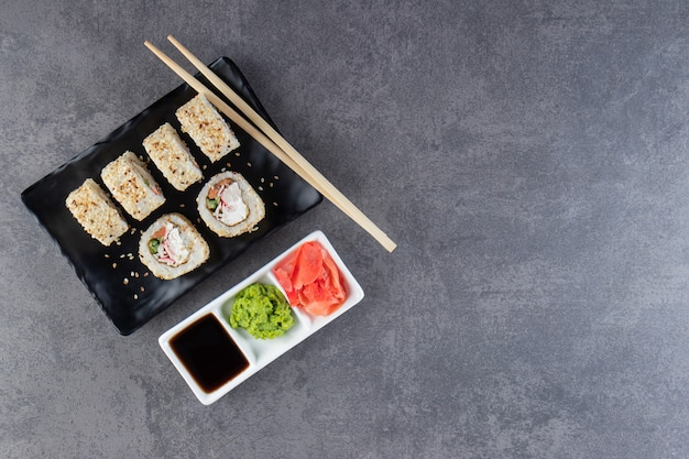Black plate of sushi rolls with sesame seeds on stone surface