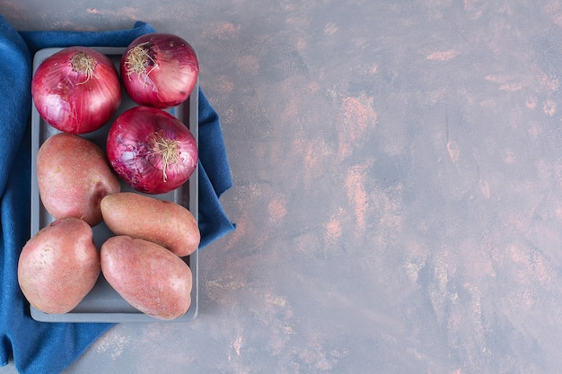 Black plate of sweet potatoes and red onions on stone background.