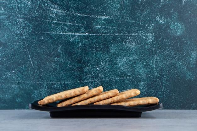 Piatto nero di gustosi biscotti posti su sfondo di pietra.