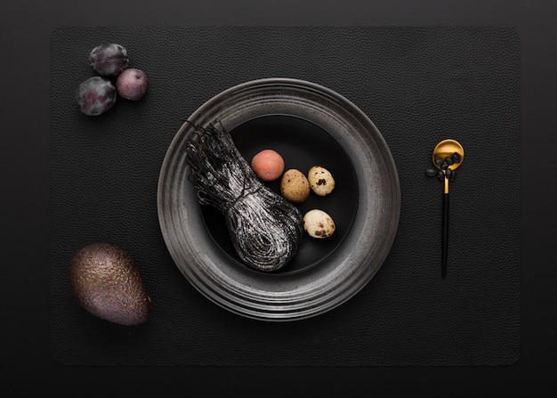 Black plate with black pasta and quail eggs on a dark background