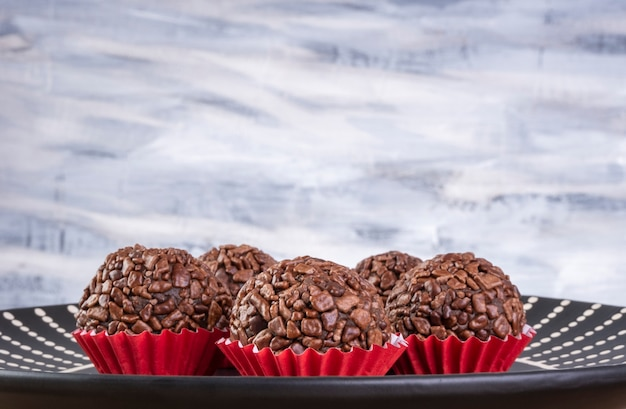 Black plate with brigadeiros on wooden table.