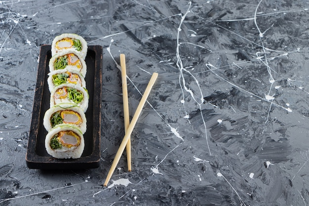 Black plate with fresh sushi rolls on marble background.