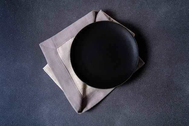 Black plate with napkin on stone table top view. space for menu or recipe.