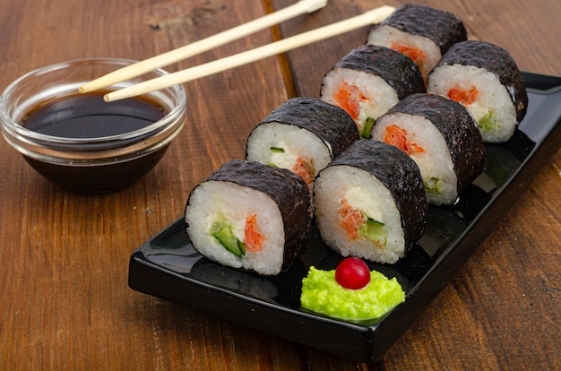 Black plate with rolls with salmon on wooden table