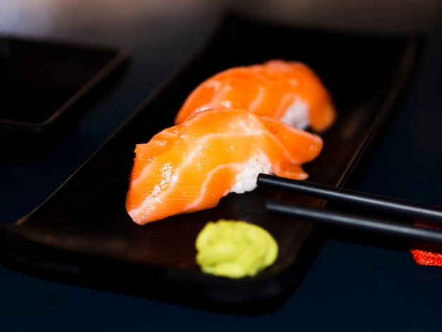 Black plate with salmon sushi and wasabi