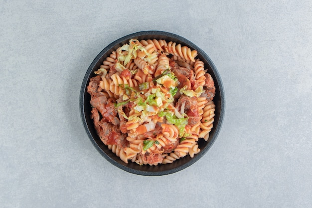 A black plate with spiral pasta with herbs .