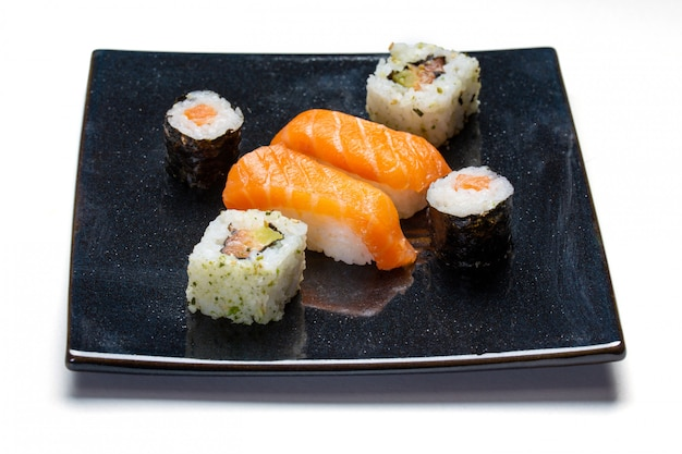 Black plate with sushi, maki and american rolls