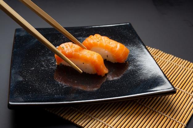 Черная тарелка с суши, маки и американскими роллами
