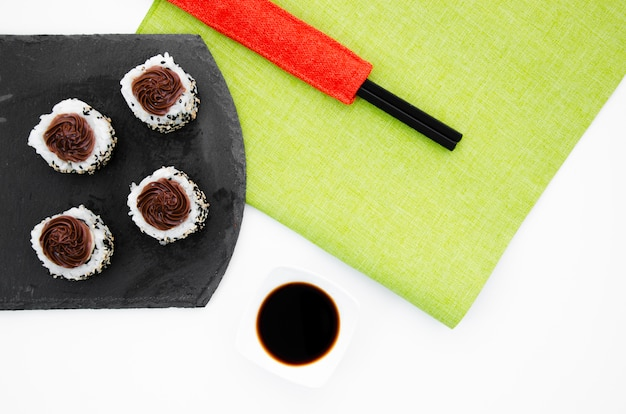 Black plate with sushi rolls on a white background with soy sauce bowl and chopsticks