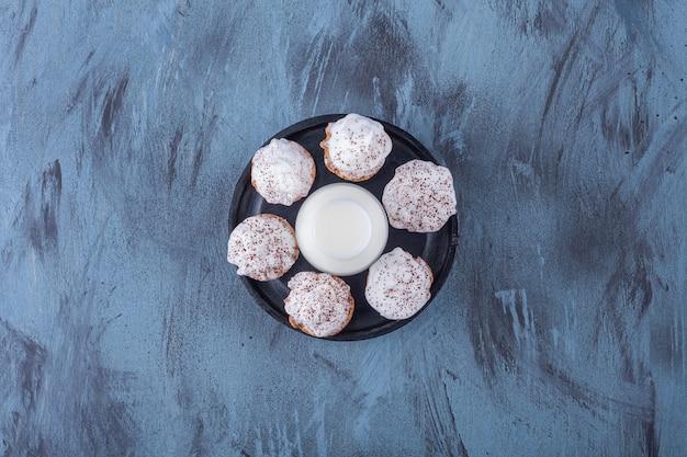 大理石の表面に甘いクリーミーなカップケーキとミルクのガラスが付いた黒いプレート。