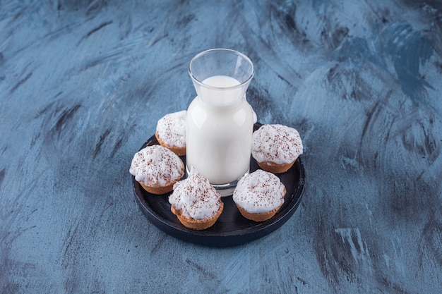 Black plate with sweet creamy cupcakes and glass of milk on marble surface.