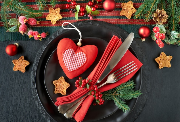 Black plates and vintage cutlery with christmas decorations on black stone