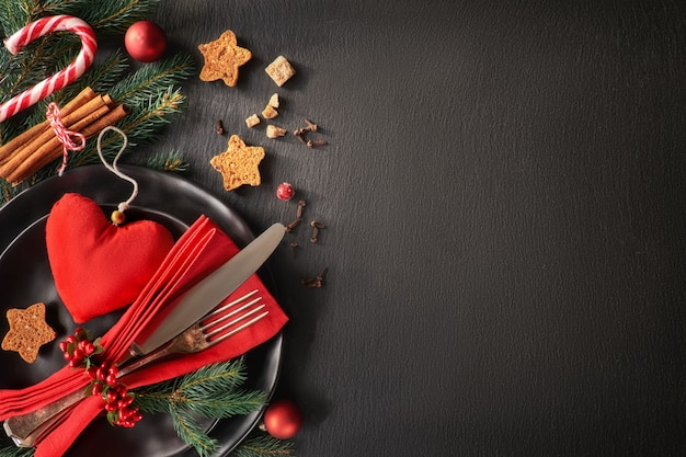 Black plates and vintage cutlery with christmas decorations, text space