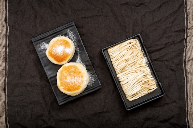 Black plates with noodles and muffins on a black cloth