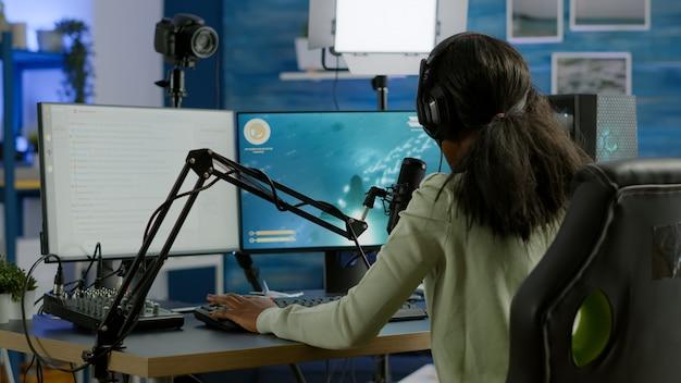 オンライントーナメントでプロのシューティングゲームをプレイしながらチャットしている他のプレイヤーと話しているヘッドフォンを身に着けている黒人プレイヤー。強力なコンピューターで新しいグラフィックを使用してオンラインビデオゲームを作成するゲーマー