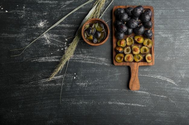 Черные сливы с соусом на деревянном блюде, вид сверху