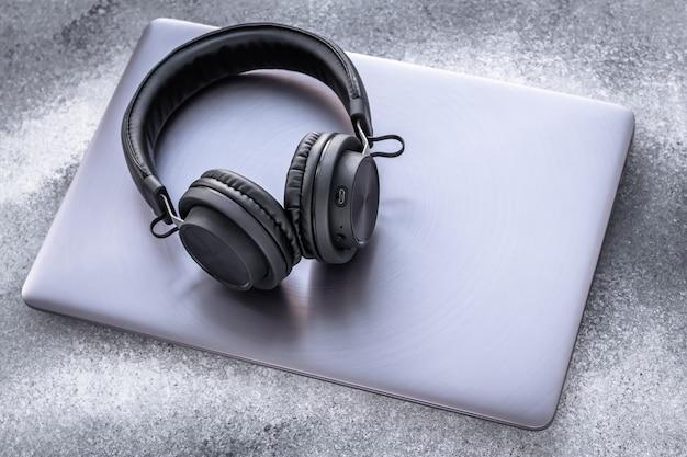 グランジ灰色の背景に紫の金属ノートに黒のポータブルヘッドフォン。灰色の背景にイヤホンで閉じたラップトップ。
